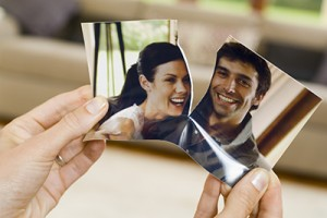 Hands ripping photograph of couple